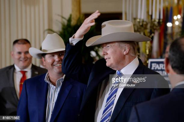 President Donald Trump examines USmade products from all 50 states including a Stetson brand hat beside Dustin Noblitt President and Chief Operating...