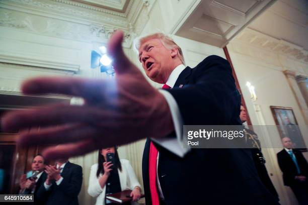 US President Donald Trump extends his hand as he stops by the National Governors Association meeting in the State Dining Room of the White House...