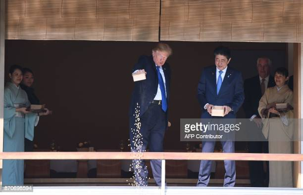 President Donald Trump feeds koi fish as Japanese Prime Minister Shinzo Abe looks on during a welcoming ceremony in Tokyo on November 6 2017 Trump...