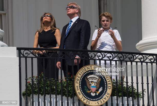US President Donald Trump First Lady Melania Trump and son Barron look up at the partial solar eclipse from the balcony of the White House in...