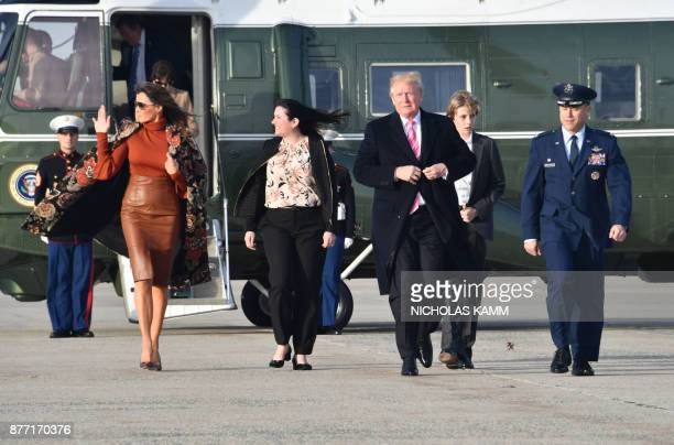 US President Donald Trump First Lady Melania Trump and son Barron Trump walk from Marine One to board Air Force One on November 21 2017 at Andrews...