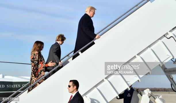 US President Donald Trump First Lady Melania Trump and son Barron Trump board Air Force One on November 21 2017 at Andrews Air Force Base Maryland /...