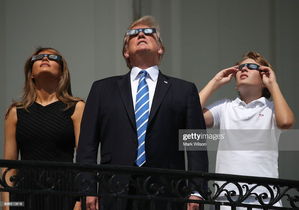 U.S. President Donald Trump, first lady Melania Trump and their son Barron Trump wear special glasses to view the solar eclipse from the Truman Balcony at the White House on August 21, 2017 in Washington, DC. Millions of people have flocked to areas of the U.S. that are in the 'path of totality' in order to experience a total solar eclipse.