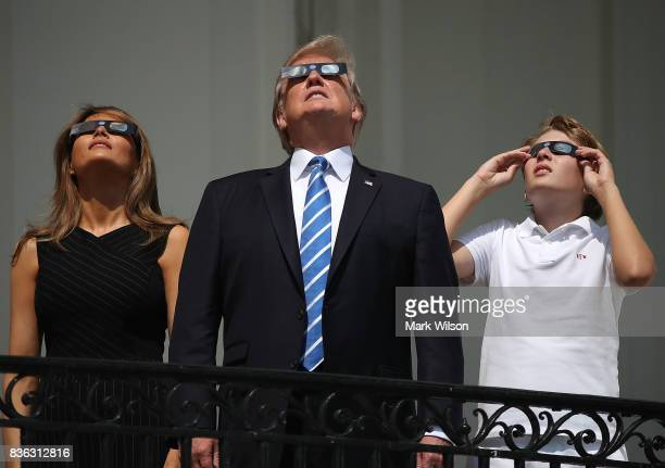 US President Donald Trump first lady Melania Trump and their son Barron Trump wear special glasses to view the solar eclipse from the Truman Balcony...
