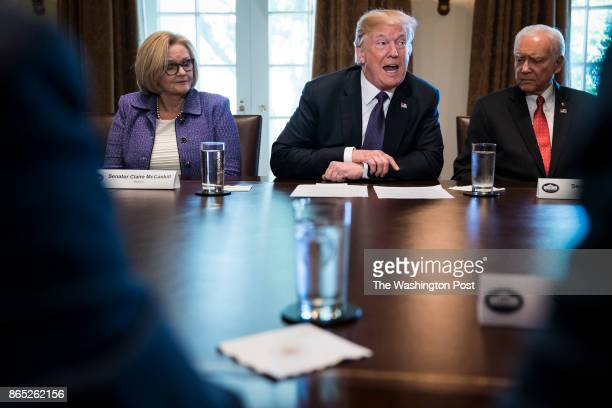 President Donald Trump flanked by Sen Claire McCaskill DMo left and Sen Orrin Hatch RUtah right speaks during a meeting with members of the Senate...