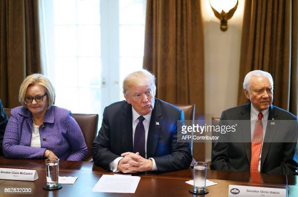 US President Donald Trump flanked by Senator Claire McCaskill DMI and Senate Finance Committee Chairman Orin Hatch RUT takes part in a meeting with...