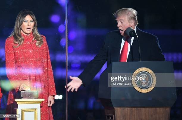 US President Donald Trump gestures as First lady Melania Trump smiles during the 95th annual National Christmas Tree Lighting ceremony at the Ellipse...