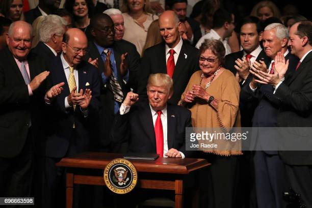 S President Donald Trump gestures as he signs policy changes he is making toward Cuba at the Manuel Artime Theater in the Little Havana neighborhood...