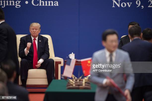 President Donald Trump gestures during a business leaders event with China's President Xi Jinping inside the Great Hall of the People in Beijing on...