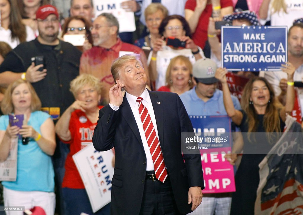 U.S. President Donald Trump gestures during a rally at the Phoenix Convention Center on August 22, 2017 in Phoenix, Arizona. An earlier statement by the president that he was considering a pardon for Joe Arpaio,, the former sheriff of Maricopa County who was convicted of criminal contempt of court for defying a court order in a case involving racial profiling, has angered Latinos and immigrant rights advocates.