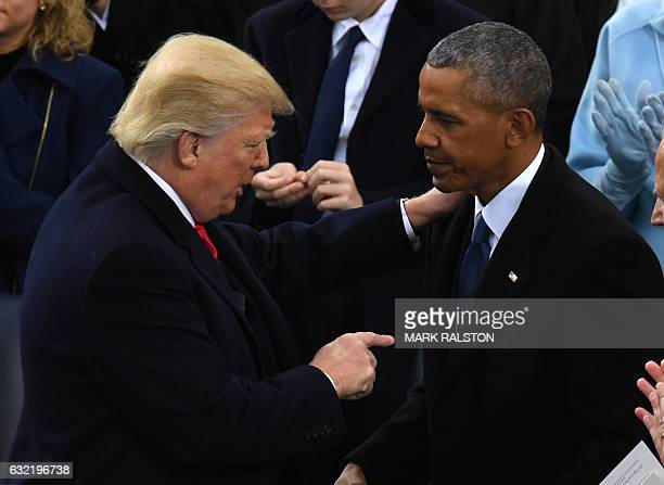 US President Donald Trump gestures to former US President Barack Obama after being sworn in as President on January 20 2017 at the US Capitol in...