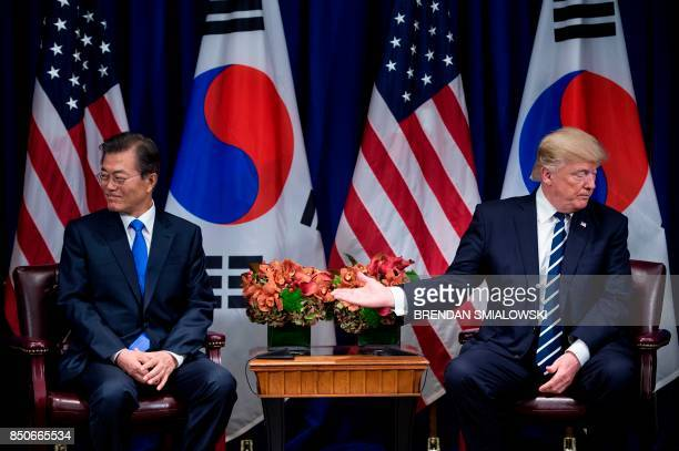 US President Donald Trump gestures to South Korea's President Moon Jaein after making a statement for the press a meeting at the Palace Hotel during...
