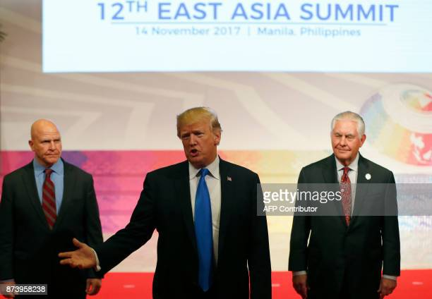 US President Donald Trump gestures to the press as US National Security Advisor HR McMaster and US Secretary of State Rex Tillerson look on after...