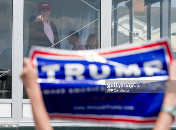 US President Donald Trump gestures to well wishers as he arrives at the 72nd US Women's Open Golf Championship at Trump National Golf Course in...