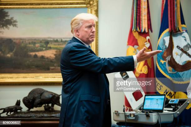 US President Donald Trump gestures toward medical equipment after speaking about new technology used by the Department of Veterans Affairs during an...