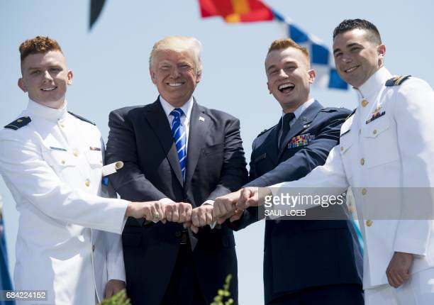 US President Donald Trump gestures with a newlycommissioned US Coast Guard Ensign and his family during the US Coast Guard Academy Commencement...