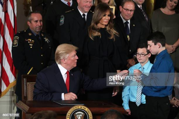 S President Donald Trump gives a signing pen to an attendee on stage as first lady Melania Trump looks on during an event highlighting the opioid...