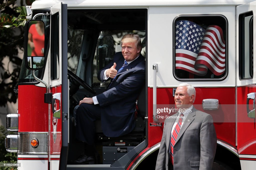 U.S. President Donald Trump gives a thumbs up to journalists from inside a fire engine made by Pierce Manufacturing while touring a Made in America product showcase with Vice President Mike Pence on the South Lawn of the White House July 17, 2017 in Washington, DC. American manufacturers representing each of the 50 states participated in the showcase, including Bully Tools, Cheerwine, Stetson, Simms and RMA Armament, Charles Machine Works, Honckley Yachts, Altec Inc., Caterpiller, Pierce Manufacturing and others.