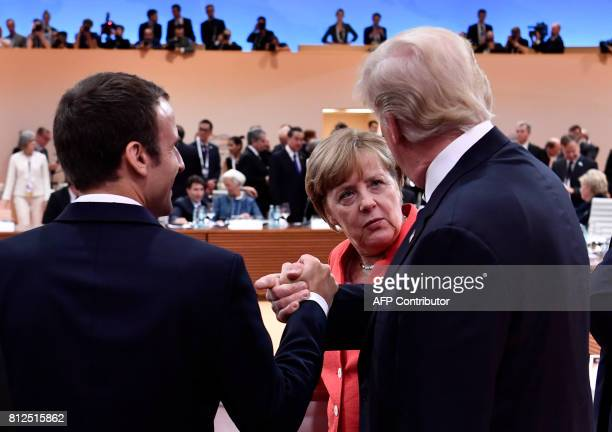 US President Donald Trump gives French President Emmanuel Macron a 'bro handshake' as they chat with German Chancellor Angela Merkel at the start of...