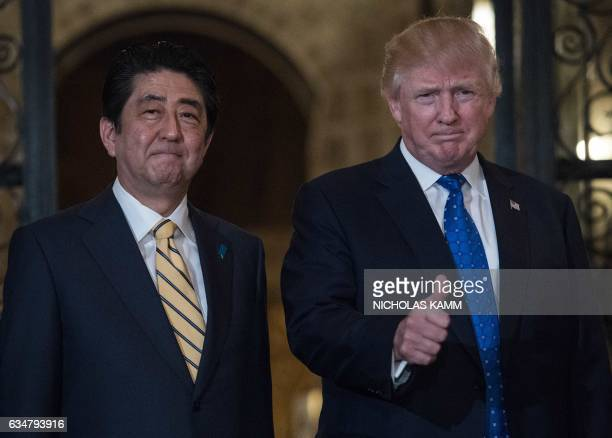 US President Donald Trump gives the thumbs up next to Japanese Prime Minister Shinzo Abe at Trump's MaraLagoresort in Palm Beach Florida on February...