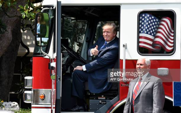 President Donald Trump gives the thumbsup sitting inside a fire truck from Wisconsinbased manufacturer Pierce as Vice President Mike Pence looks on...