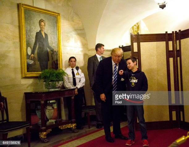 S President Donald Trump greets Jack Cornish a White House visitor in a corridor of the White House while a portrait of Hillary Clinton hangs on the...