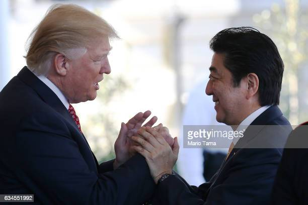 President Donald Trump greets Japan's Prime Minister Shinzo Abe as he arrives at the White House on February 10 2017 in Washington DC The two will...