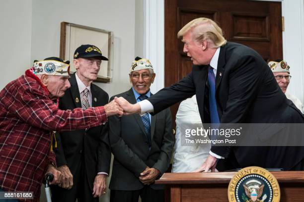President Donald Trump greets Lawrence Parry before signing a proclamation for National Pearl Harbor Remembrance Day with survivors of the attack...
