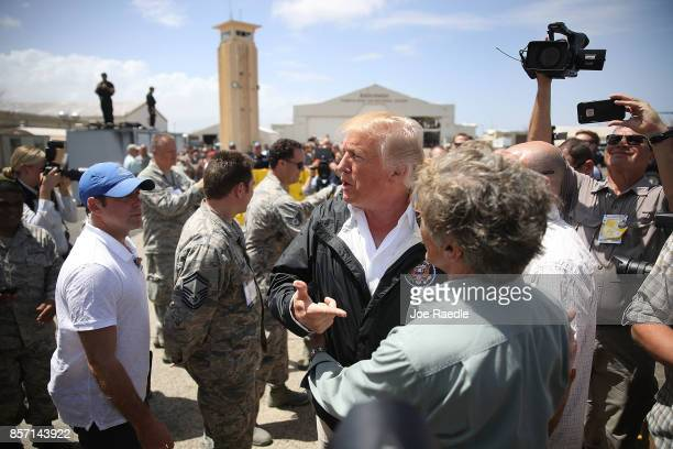 President Donald Trump greets people as he arrives at the Muniz Air National Guard Base for a visit after Hurricane Maria hit the island on October 3...