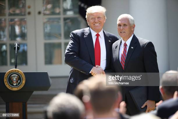 S President Donald Trump greets US Vice President Mike Pence before announcing his decision for the United States to pull out of the Paris climate...