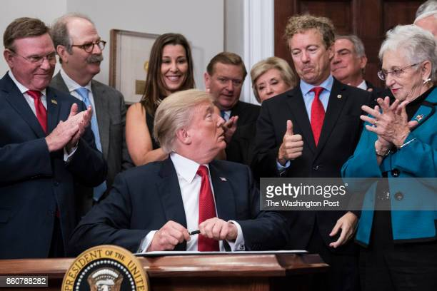 President Donald Trump hands a pen that he used to sign an executive order on health care to Sen Rand Paul RKy in the Roosevelt Room at the White...