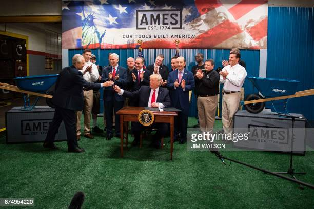 US President Donald Trump hands a pen to Director of the National Trade Council Peter Navarro after signing an Executive Order on the Establishment...