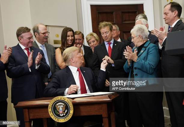 US President Donald Trump hands a pen to Senator Rand Paul RKY after using it to sign an executive order on health insurance on October 12 2017 in...