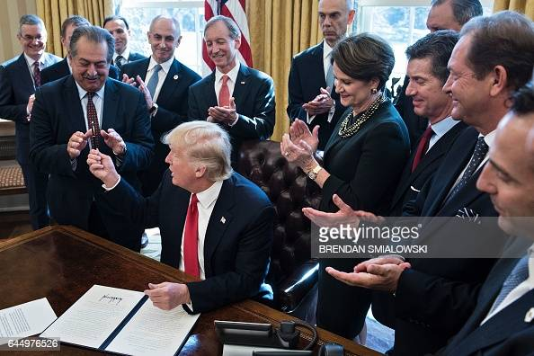 US President Donald Trump hands Andrew N Liveris CEO of Dow Chemical the pen after signing an executive order about regulatory reform in the Oval...