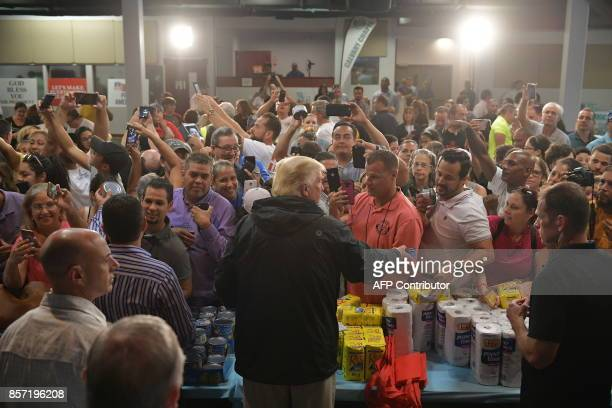 US President Donald Trump hands out supplies as he visits the Cavalry Chapel in Guaynabo Puerto Rico on October 3 2017 Nearly two weeks after...