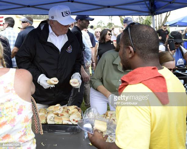 US President Donald Trump helps serve food to people affected by Hurricane Irma in Naples Florida on September 14 2017 / AFP PHOTO / Brendan...