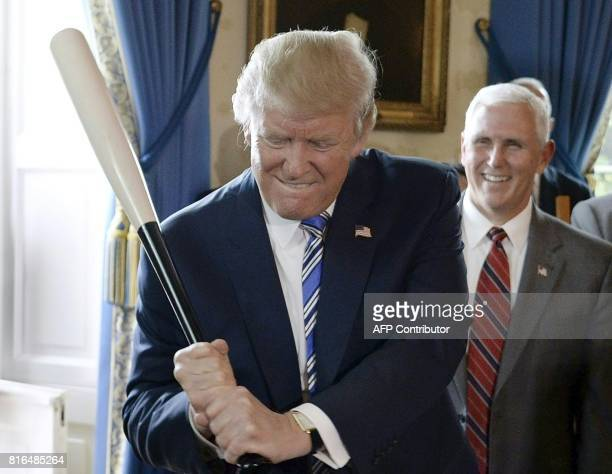 President Donald Trump holds a Marucci baseball bat as Vice President Mike Pence looks on in the Blue Room during a 'Made in America' product...