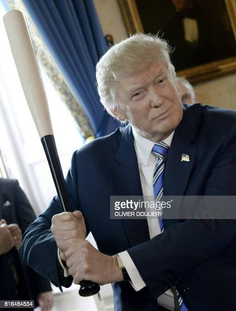 President Donald Trump holds a Marucci baseball bat in the Blue Room during a 'Made in America' product showcase event at the White House in...