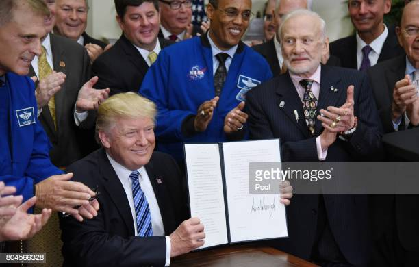 US President Donald Trump holds a signed Executive Order to reestablish the National Space Council as Apollo 11 astronaut Buzz Aldrin looks on in the...