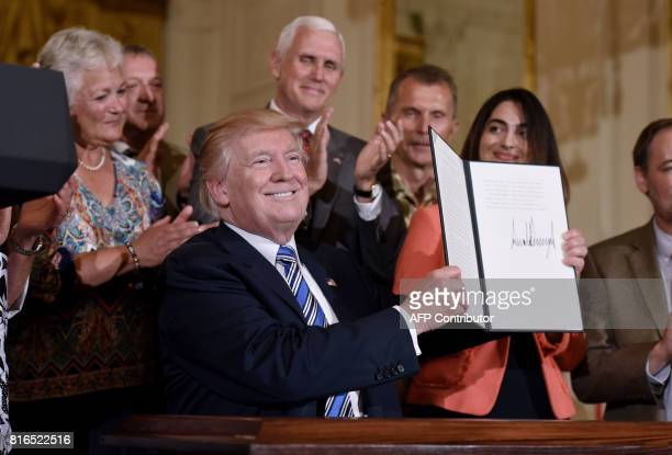 President Donald Trump holds a signed proclamation designating July 17 'Made in America Day' during a Made in America product showcase event at the...