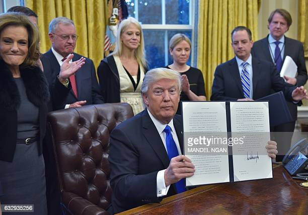 US President Donald Trump holds an executive memorandum on defeating the Islamic State in Iraq and Syria after signing it in the Oval Office of the...