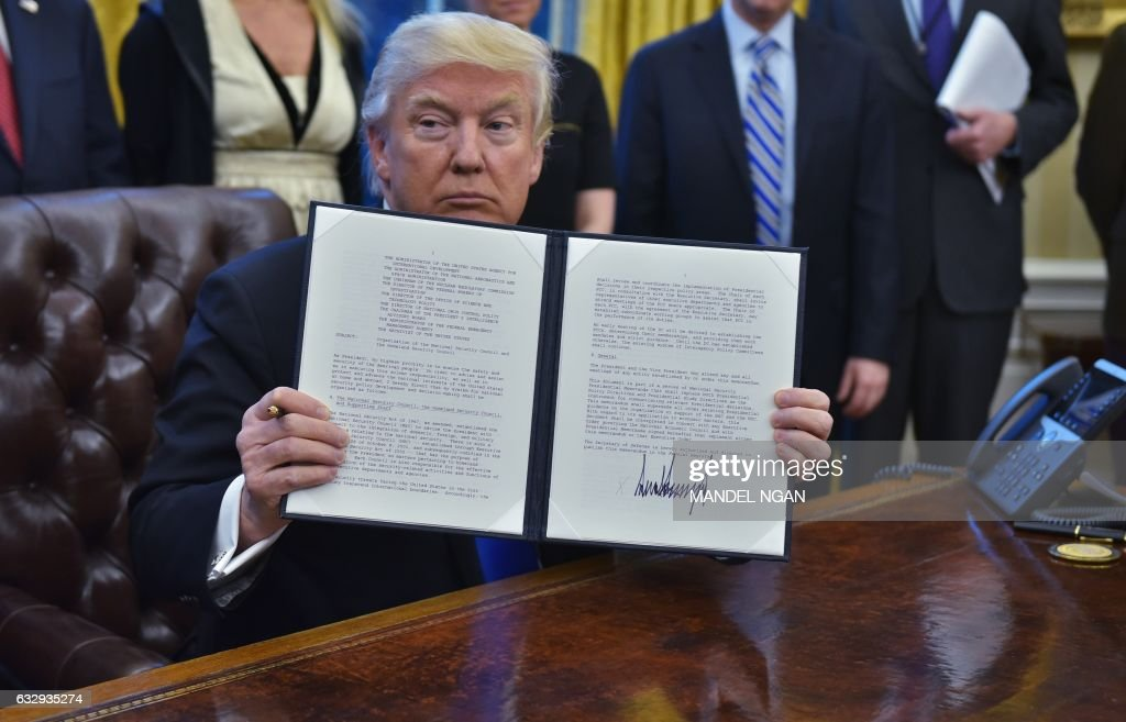 US President Donald Trump holds an executive memorandum on defeating the Islamic State in Iraq and Syria after signing it in the Oval Office of the White House on January 28, 2017, in Washington, DC. US Vice President Mike Pence (L), National Security Advisor Michael Flynn (C) and Counselor to the President Kellyanne Conway (R) joined Trump. /