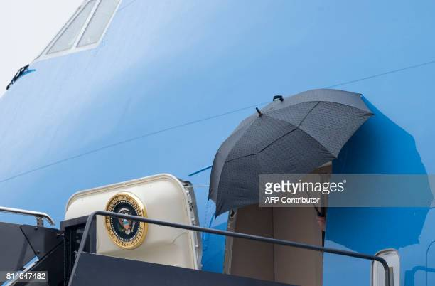 US President Donald Trump holds an umbrella as he disembarks from Air Force One upon arrival at Newark Liberty International Airport in Newark New...