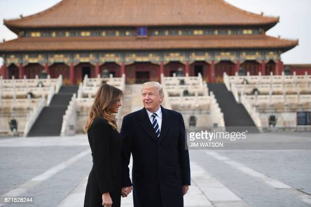 US President Donald Trump holds hands with First Lady Melania Trump in the Forbidden City in Beijing on November 8 2017 US President Donald Trump...