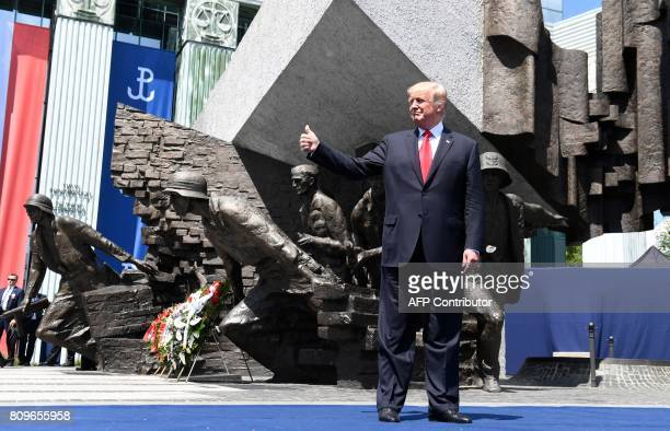 President Donald Trump holds his thumb up as he poses in front of the Warsaw Uprising Monument on Krasinski Square on the sidelines of the Three Seas...