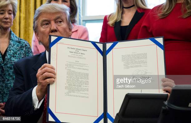 S President Donald Trump holds HR 321 after signing it in The Oval Office at The White House on February 28 2017 in Washington DC President Trump...