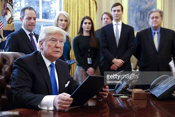 US President Donald Trump holds one of five executive orders related to the oil pipeline industry in the Oval Office of the White House in Washington...