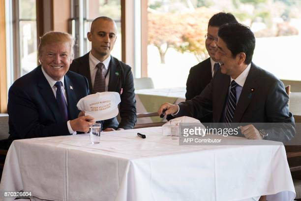 US President Donald Trump holds up a hat as he speaks with Japan's Prime Minister Shinzo Abe during a luncheon at the Kasumigaseki Country Club Golf...