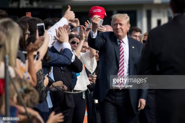 President Donald Trump holds up a 'Make America Great Again' hat while greeting onlookers before boarding Marine One on the South Lawn of the White...