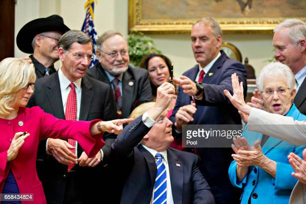 US President Donald Trump holds up a pen to give away after signing HJ Res 57 which overturns a rule on school accountability standards that are part...